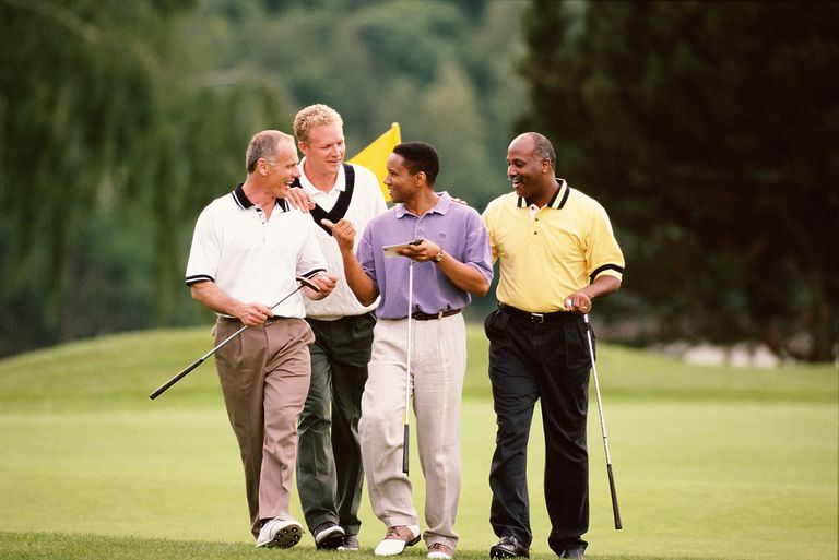Four golfers walk off putting green together