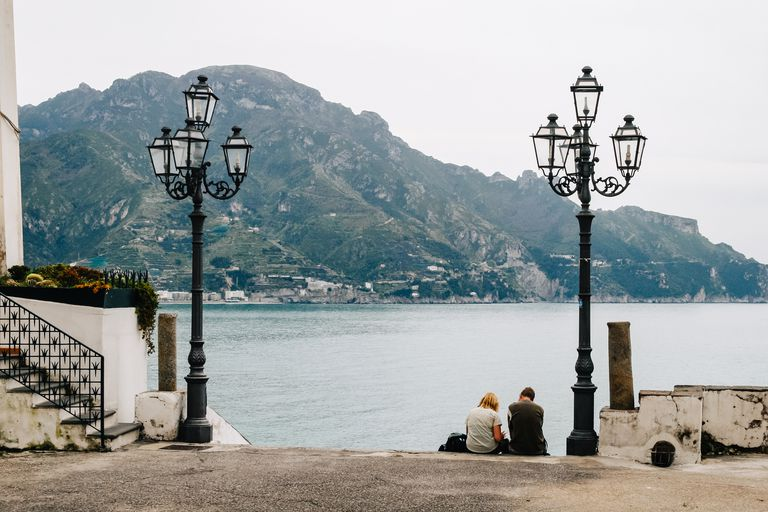 Rear View Of People Sitting By Antique Street Light In Atrani, Italy