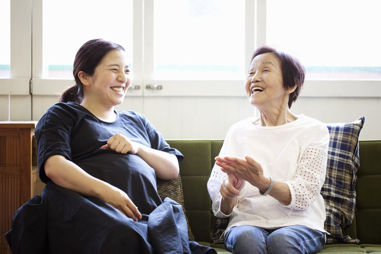 two women talk on sofa