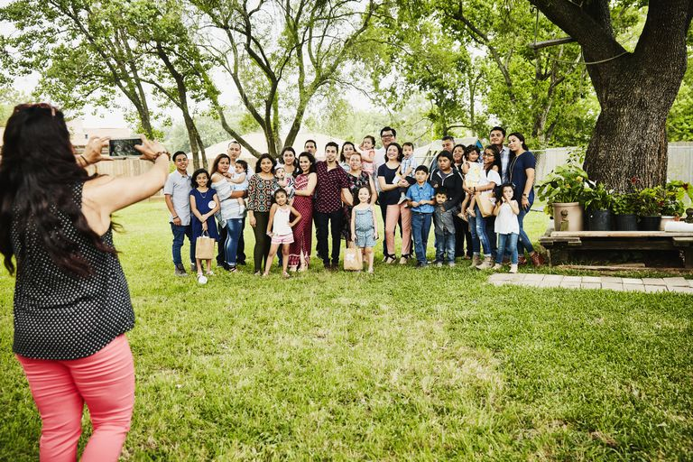 Woman taking photo of smiling multigenerational family gather for backyard birthday party