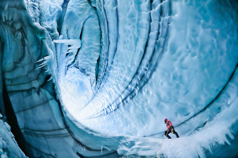 An explorer beholds the massive ice formations of a dramatic glacier