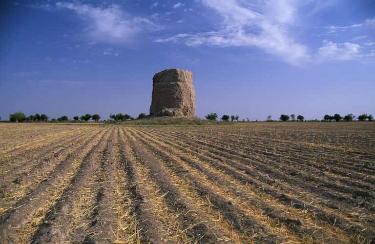 A Buddhist stupa rises over a field in Uzbekistan