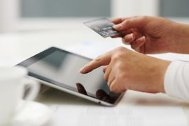 Woman using a tablet to enter credit card numbers