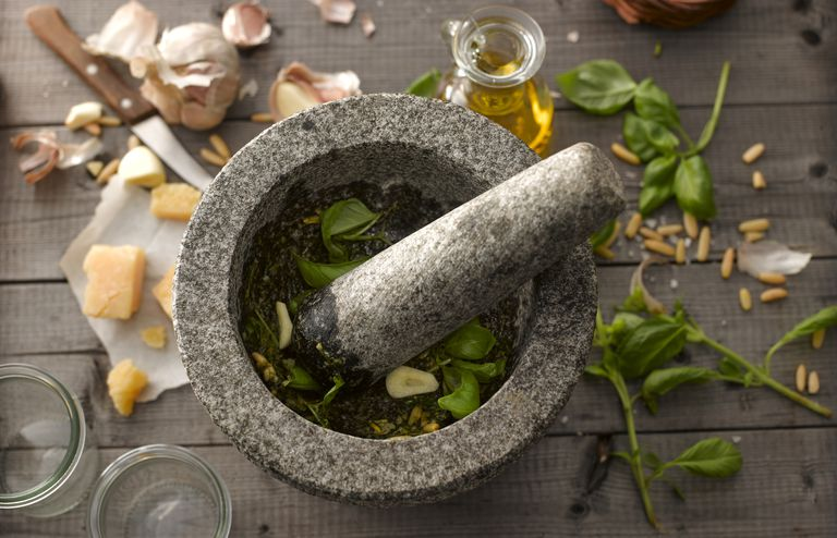 Preparing basil pesto with mortar