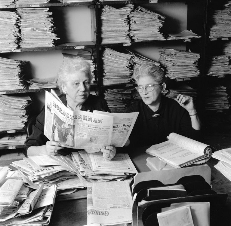 Historical photo of two women in a periodical room at a library, going through old newspapers