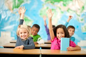first grade class students raising hands smiling