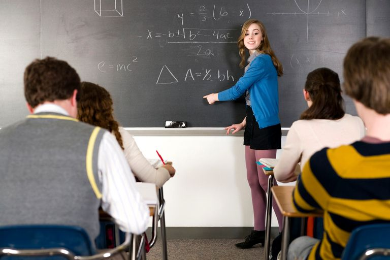 Student solving a tenth grade math problem on a classroom chalkboard