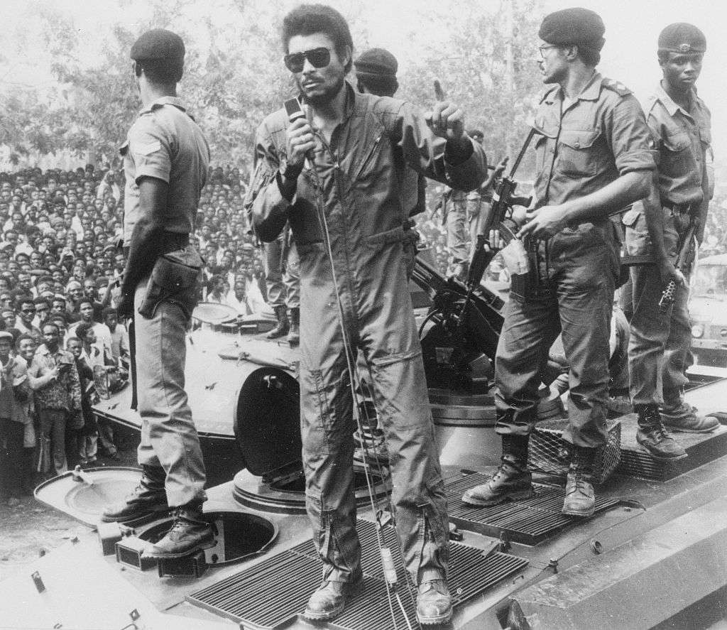 Jerry Rawlings en su traje de vuelo hablando por un micrófono