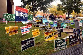 Political signs on a large lawn.