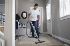 Man vacuuming rug at front entrance of home