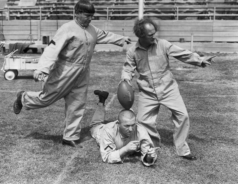 The Three Stooges clowning with a football on a football field
