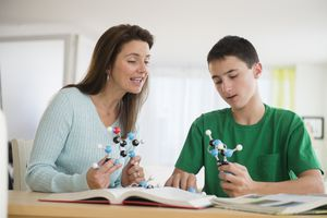 Mother and son working on science homework at a table