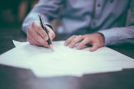 Close up of a man signing letters on his desk.