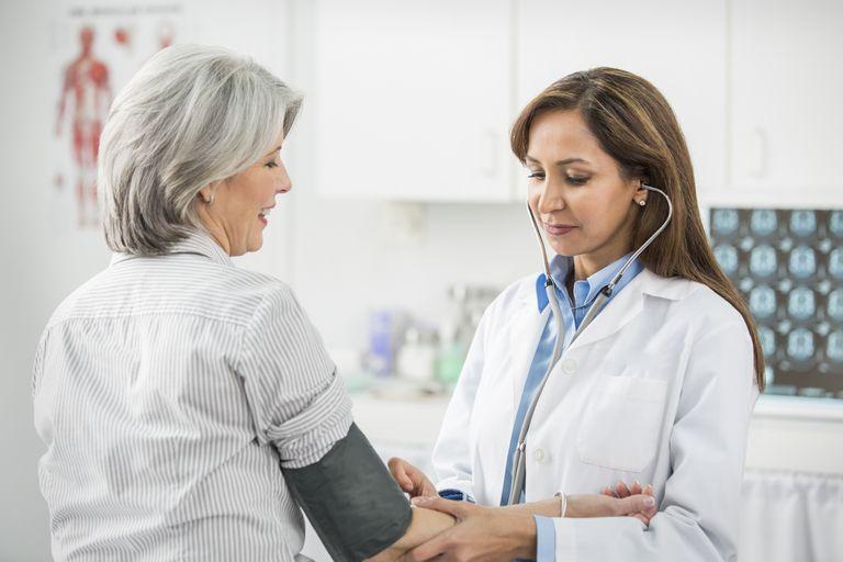 Doctora toma la presión arterial a paciente