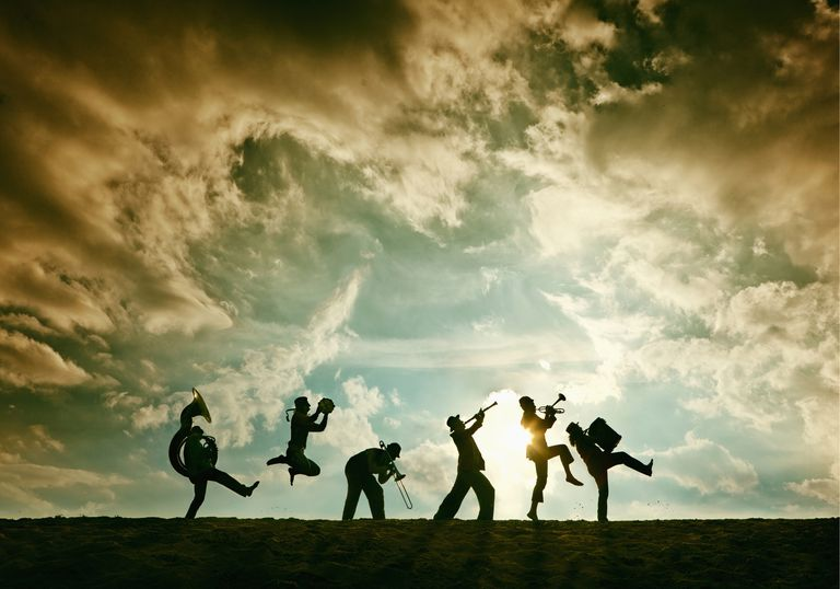 silhouette of brass band on sand dune