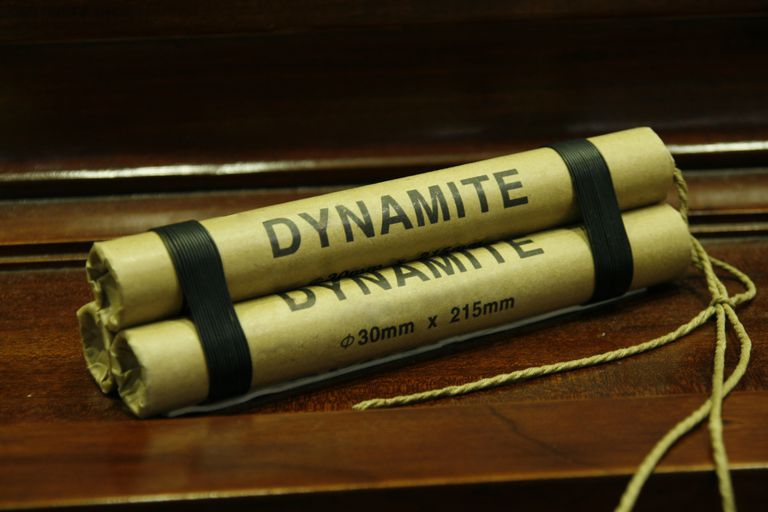 Dynamite stick isolated on wooden table