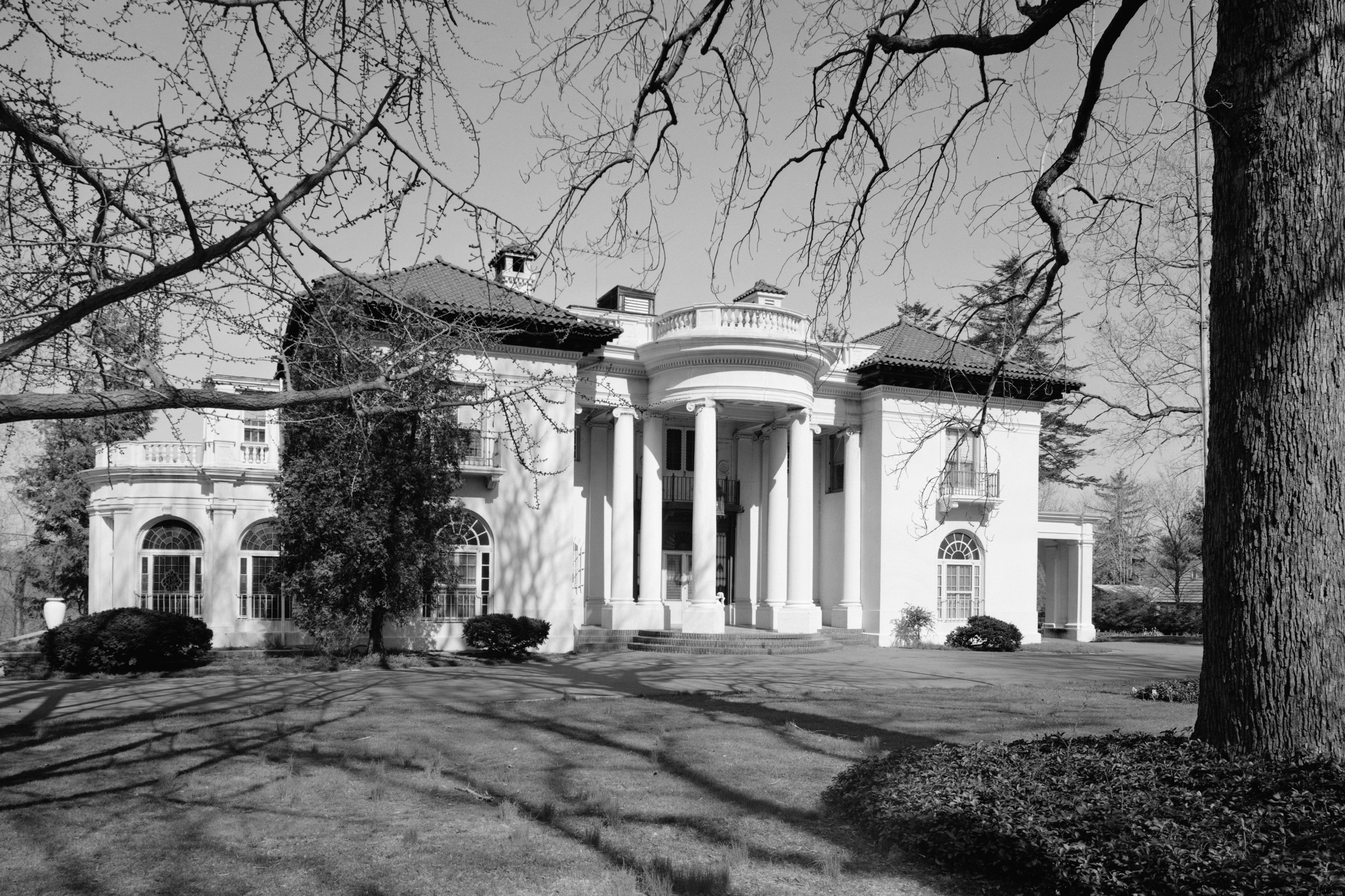 black and white photo of mansion with columns