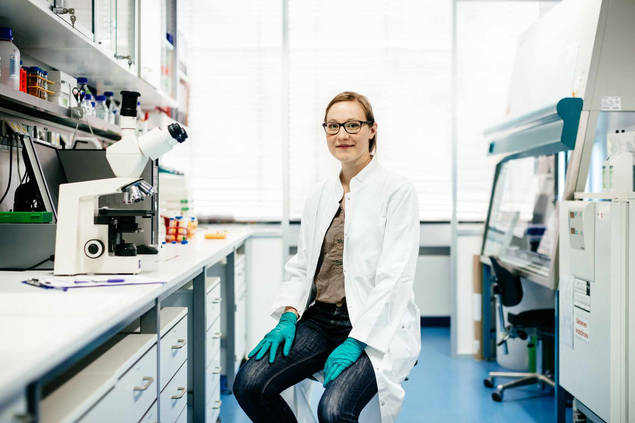 Seated woman wearing lab coat