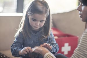 Girl sticking bandaid onto mothers hand from first aid kit