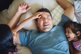 children waking up man in bed