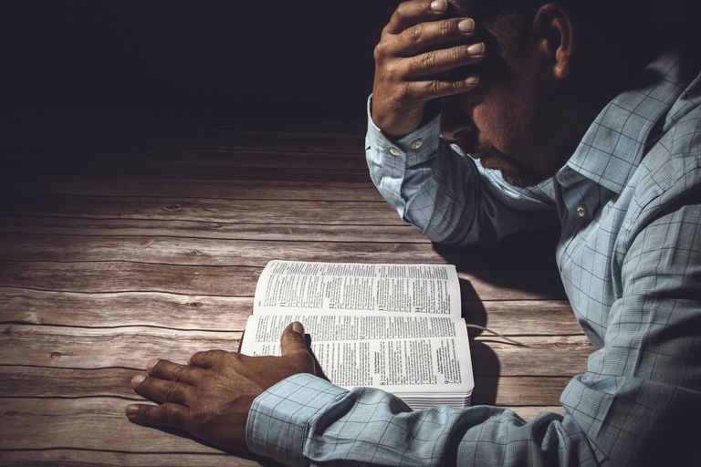 Worried man reading the Holy Bible
