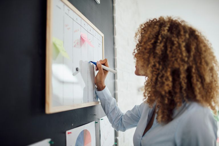 Latina Businesswoman Writing Schedule.