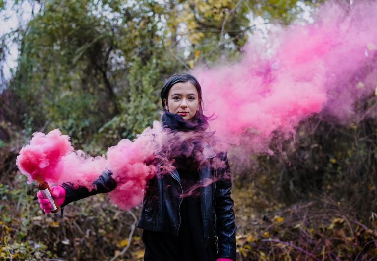 Girl holding a colored smoke bomb