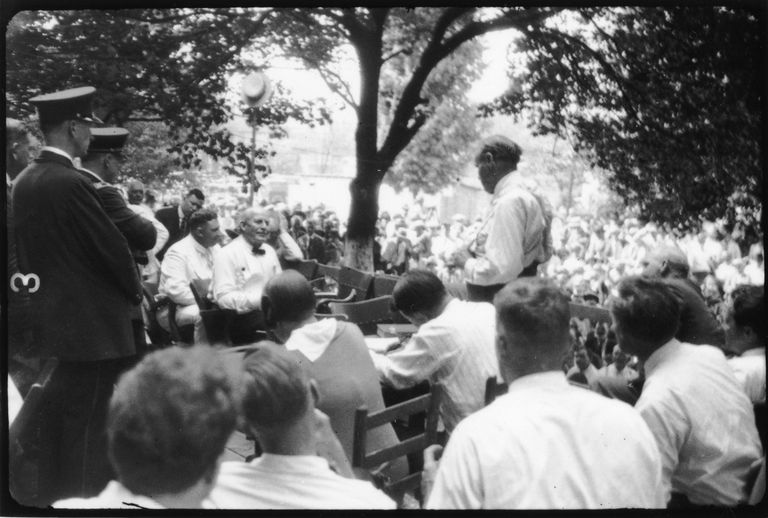 view of the Scopes Trial once it was moved outside the courthouse, with William Jennings Bryan seated at left and Clarence Darrow standing on the right.
