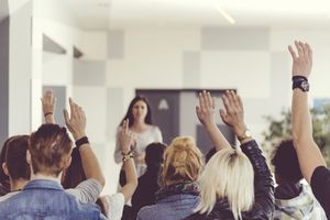 Teacher in front of a class with their hands up
