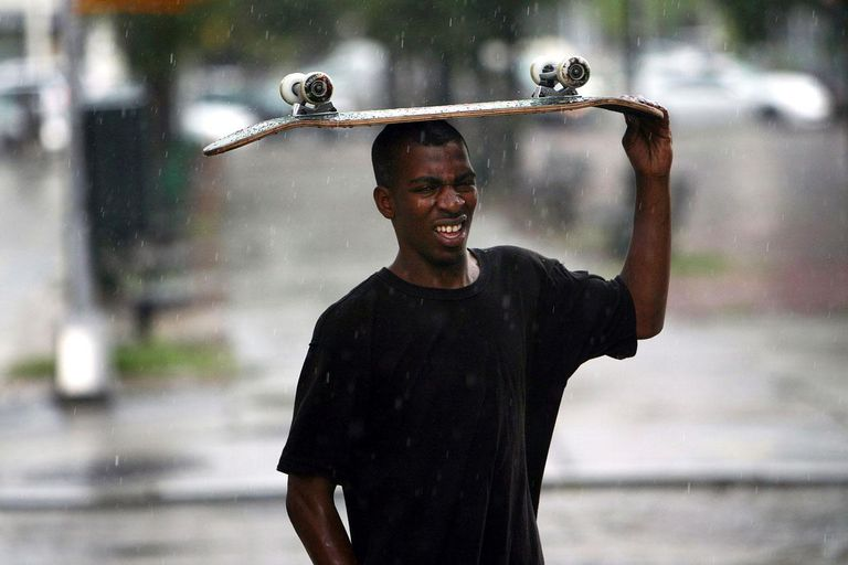 NEW YORK - JULY 27: A teenager attempts to use his skateboard to keep dry during an afternoon thunderstorm on July 27, 2009 in New York, New York. During severe weather yesterday, lightning injured four men, one critically, during a strike in Newark.