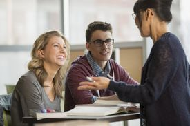 Professor talking to college students at table