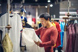 Fashion and Consumerism Concept.Smart man with beard choosing clothes in clothing store at shopping center, looking for new shirts design that hanging on the rail