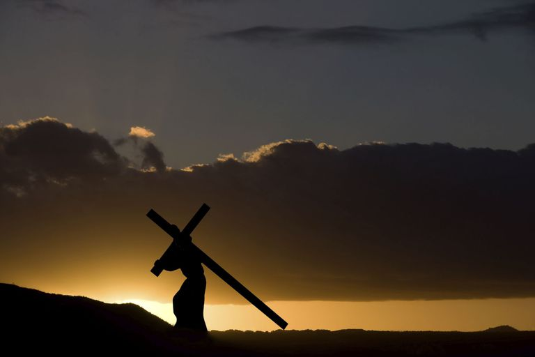 Silhouette of a man carrying a large cross at twilight