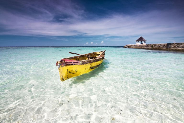 Fishing canoe docked at a beach in clear shallow water, north coast Jamaica.