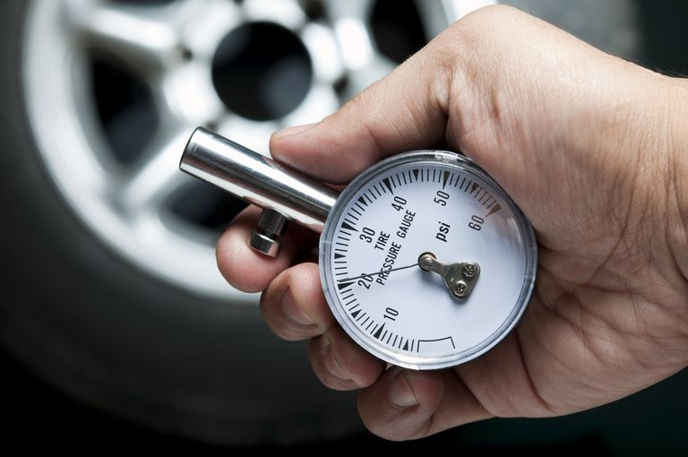 checking tire pressure with gauge