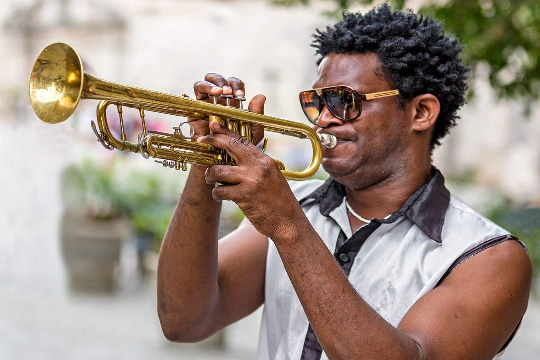 Cuba, Havana, Plaza de San Francisco de Asis, Cuban trumpet player entertains passers by.