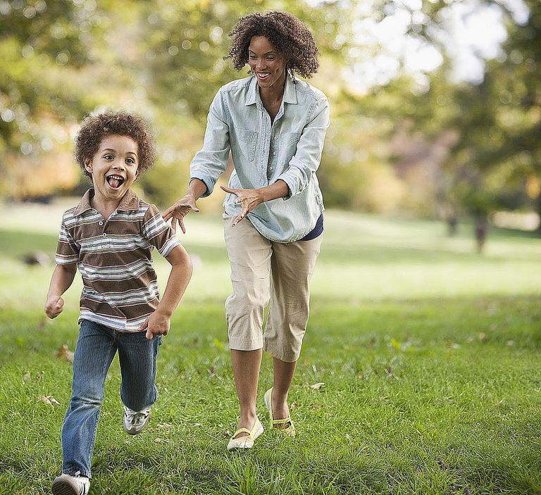 Mother and son running in park