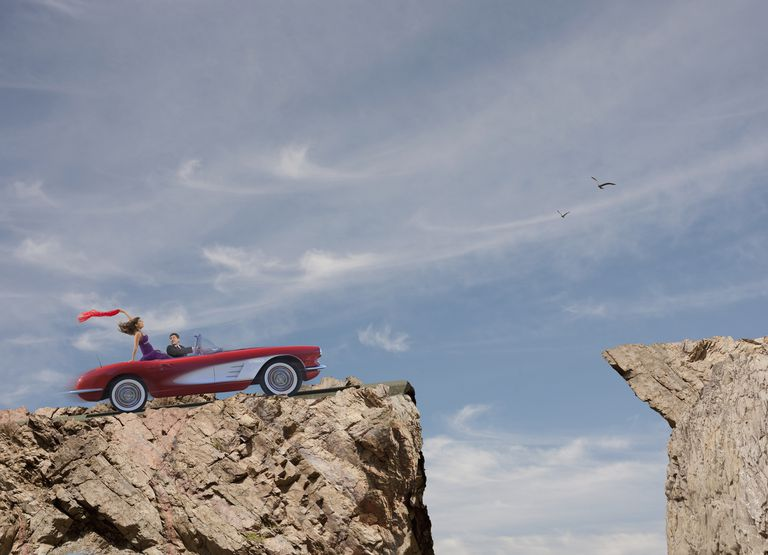 Oblivious couple driving convertible over cliff