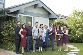 Multi-generation family posing near house