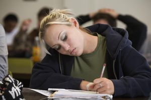 Mixed race college student taking notes in classroom