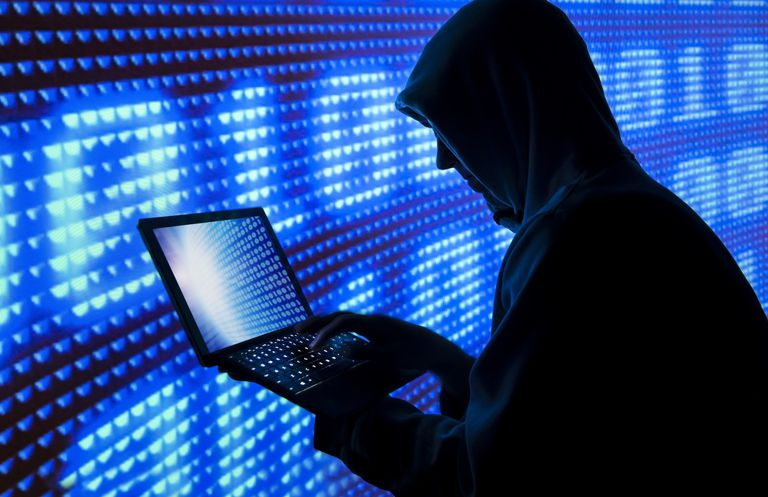 Hacker in hoodie holding a laptop in front of giant digital display screen\