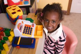 A child playing with toy cash register and smiling up at the camera.