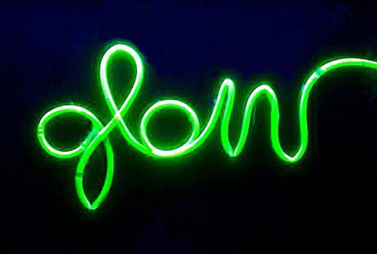You can make a glowing fake neon sign using plastic tubing and a black light.