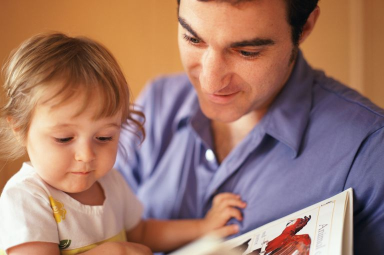 Father and daughter (18-24 months) looking at book