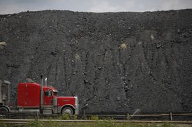 Semi truck passing in front of a mound of newly-mined coal