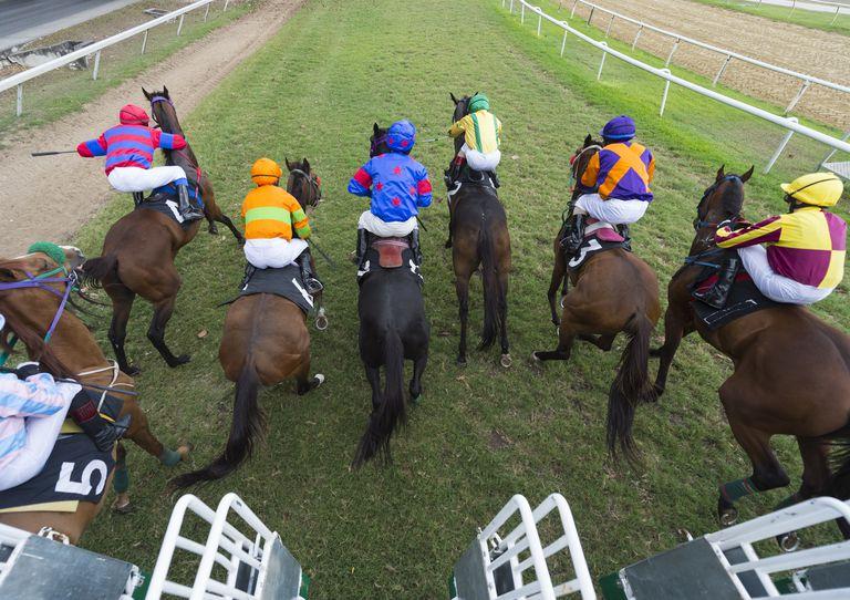 jockeys riding horses at a track