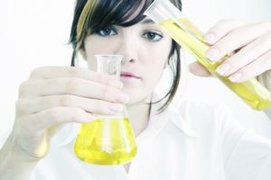 Young woman in lab coat holding flask and test tube containing yellow liquid