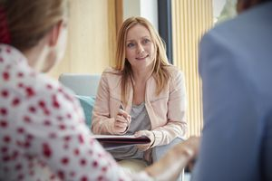 A female therapist listens to a couple during a therapy session.