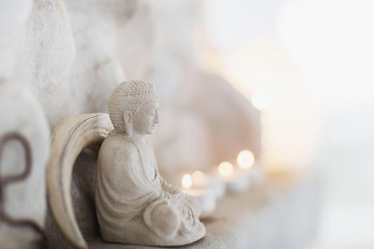 Buddha figurine and candles on ledge