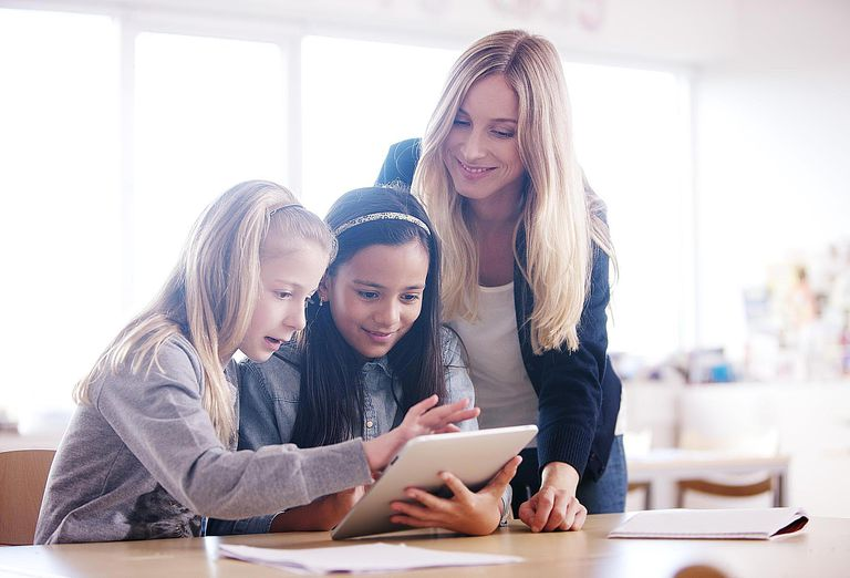 Two girls using tablet computer, teacher watching